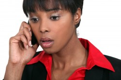 A businesswoman getting bad news on the phone.