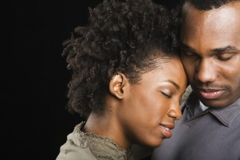 African American couple hugging with eyes closed